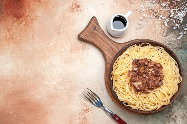 上面図木製の机の上のひき肉と調理されたスパゲッティパスタ生地の肉