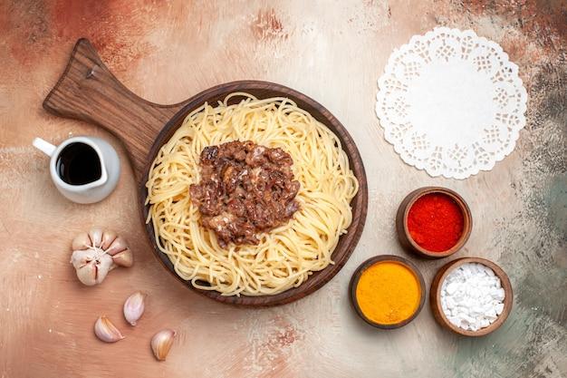 上面図木製の机の上のひき肉と調理されたスパゲッティパスタ生地料理の調味料
