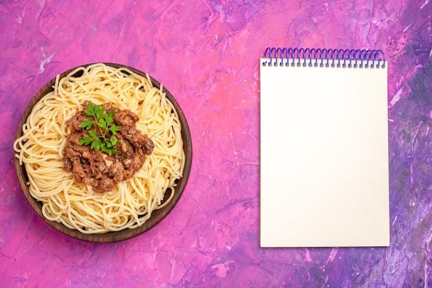 ピンクの机の生地の食事パスタ皿にひき肉とトップビュー調理されたスパゲッティ