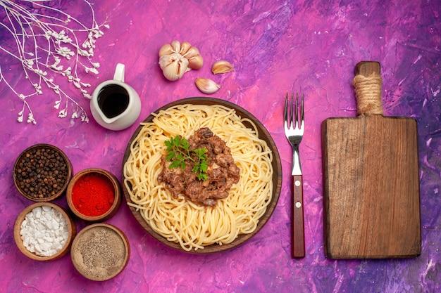ピンクの机の調味料皿生地パスタにひき肉とトップビュー調理されたスパゲッティ