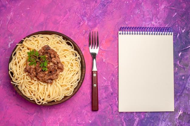 上面図ピンクのテーブルの色の皿生地パスタにひき肉と調理されたスパゲッティ