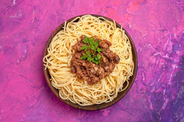 ピンクのテーブル生地ミールパスタ皿にひき肉と一緒に調理されたスパゲッティの上面図