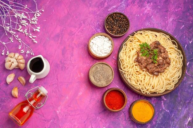 분홍색 테이블 조미료 반죽 파스타에 갈은 고기를 곁들인 상위 뷰 요리 스파게티