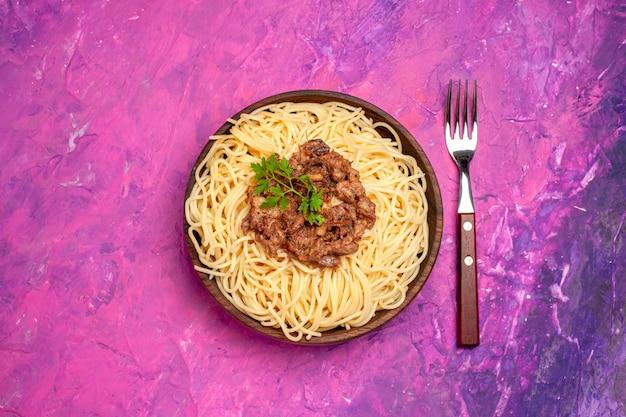 Spaghetti cucinati vista dall'alto con carne macinata su pasta di pasta per piatti di colore rosa da tavola