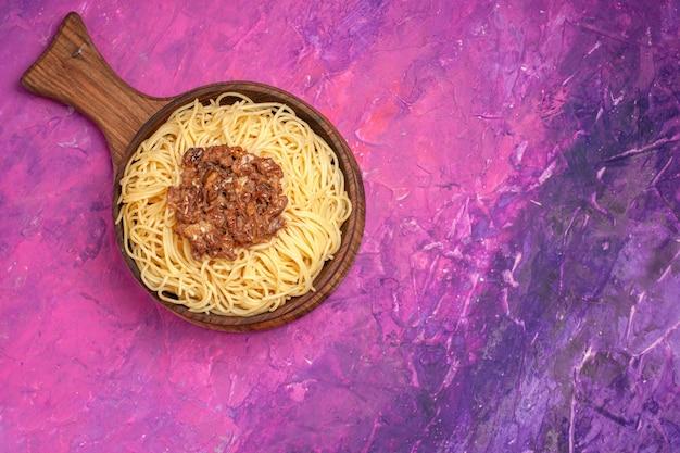 Spaghetti cotti vista dall'alto con carne macinata su condimento per pasta piatto da tavola rosa