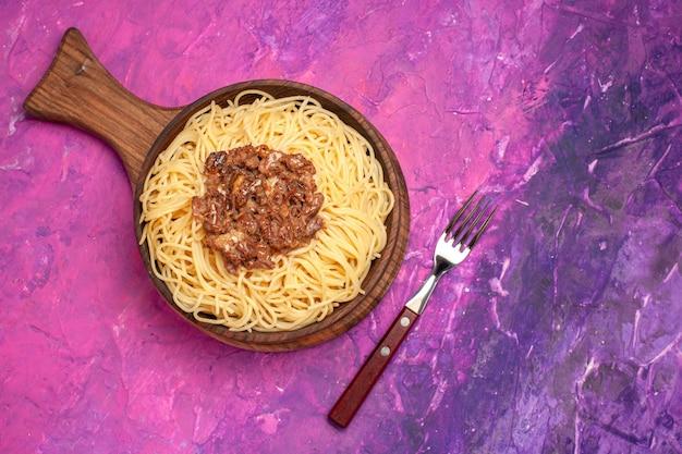 Spaghetti cotti vista dall'alto con carne macinata su condimento per pasta da tavola rosa