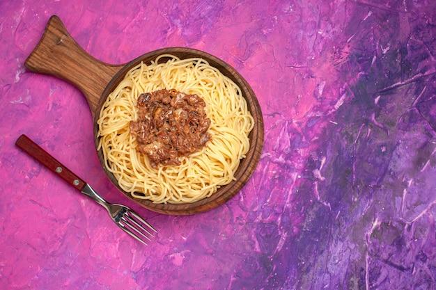 Spaghetti cucinati vista dall'alto con carne macinata sul condimento per piatti di pasta rosa da tavola