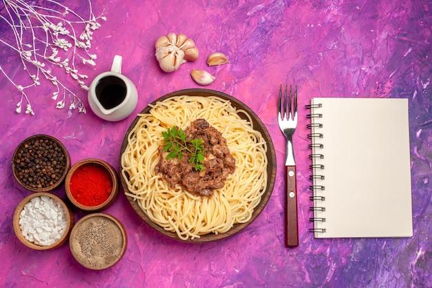 Spaghetti cucinati vista dall'alto con carne macinata su pasta rosa per condimenti da tavola