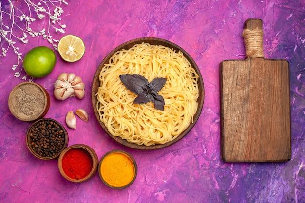Вид сверху приготовленные спагетти с приправами на блюдо из пасты из розового столового теста
