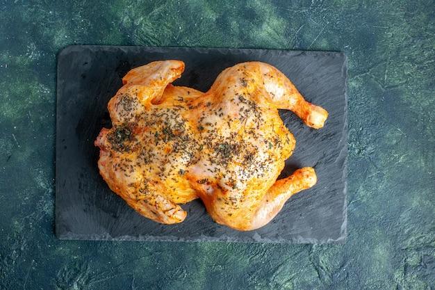 Вид сверху приготовленной курицы со специями на темной поверхности