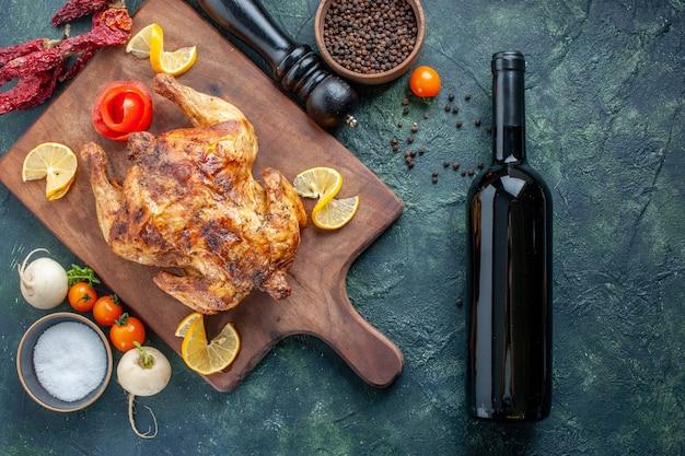 Pollo speziato cotto vista dall'alto con bottiglia di vino su superficie blu scuro
