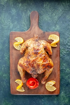 Pollo speziato cotto vista dall'alto con limone su superficie scura