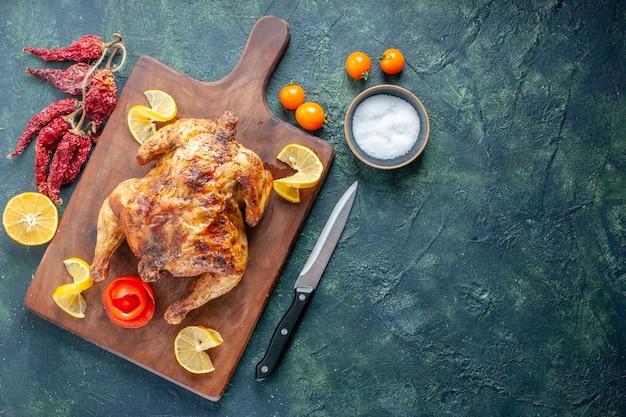 Pollo speziato cotto vista dall'alto con fette di limone su superficie scura