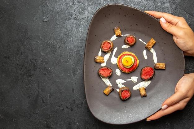Vista dall'alto di zucche cotte progettato pasto all'interno del piatto sulla superficie grigia
