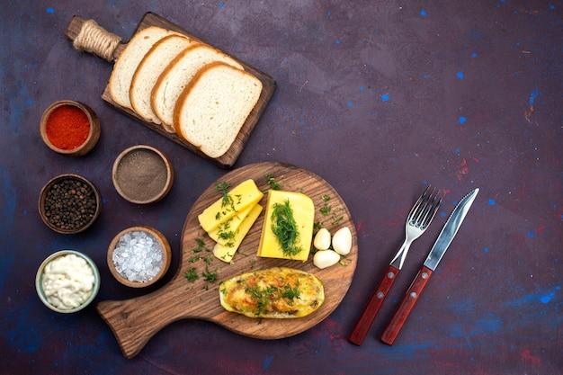 Vista dall'alto cotte gustose zucche con condimenti, formaggio e pagnotte di pane sulla scrivania viola scuro.