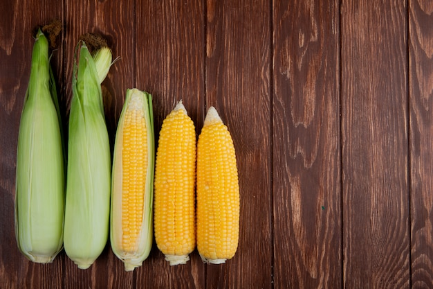 Top view of cooked and uncooked corn cobs on left side and wooden surface with copy space