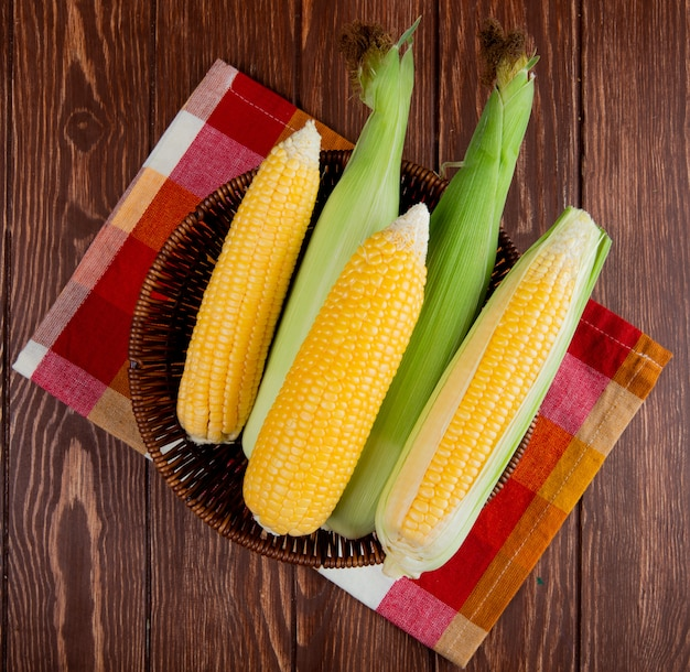 Top view of cooked and uncooked corns in basket on cloth and wooden surface