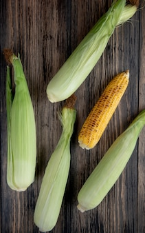Top view of cooked and uncooked corns on wooden surface 1