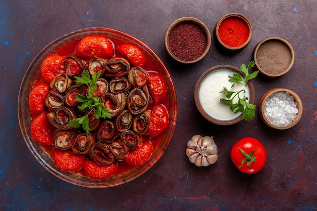 어두운 표면에 조미료 사워 크림과 함께 상위 뷰 요리 야채 식사 맛있는 토마토와 가지
