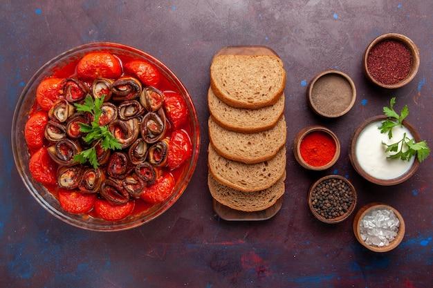 Vista dall'alto farina di verdure cotte deliziosi pomodori e melanzane con pane e condimenti sulla superficie scura