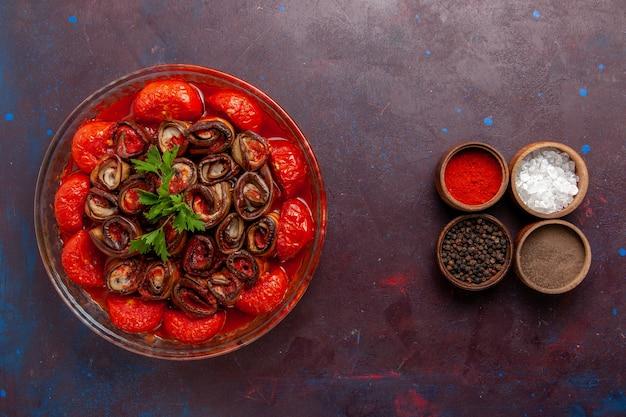 Vista dall'alto farina di verdure cotte deliziosi pomodori e melanzane con condimenti sul pavimento scuro che cucinano cibo pasto cena piatto