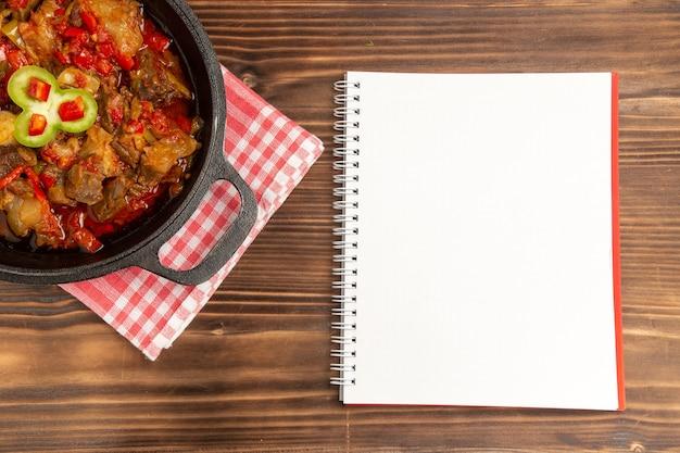 Вид сверху приготовленной овощной еды, включая овощи и мясо внутри на коричневом столе