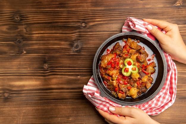 Вид сверху приготовленной овощной еды внутри сковороды на коричневом столе