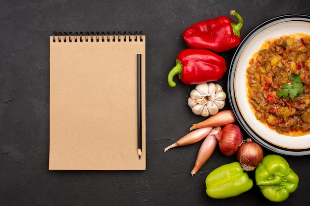 Вид сверху приготовленной овощной еды внутри тарелки со свежими овощами на сером фоне блюдо еды еды