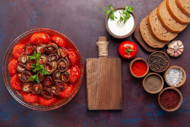 Вид сверху приготовленные овощные блюда из помидоров и баклажанов с приправами и буханками хлеба на темном столе