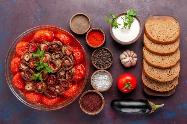 Вид сверху приготовленные овощные блюда из помидоров и баклажанов с приправами и хлебом на темном столе