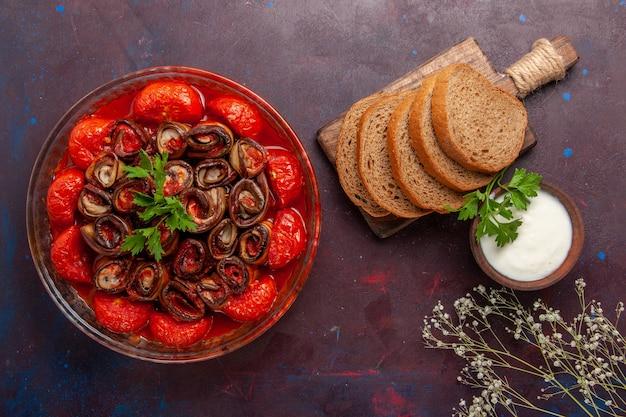 Vista dall'alto farina di verdure cotte pomodori e melanzane con pagnotte di pane sulla superficie scura