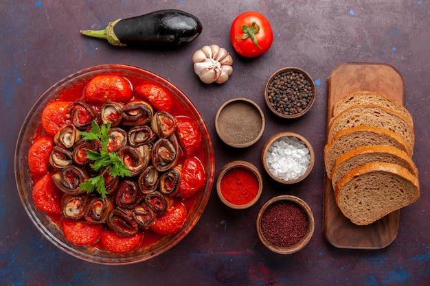 Vista dall'alto farina di verdure cotte pomodori e melanzane con pane e condimenti sulla superficie scura