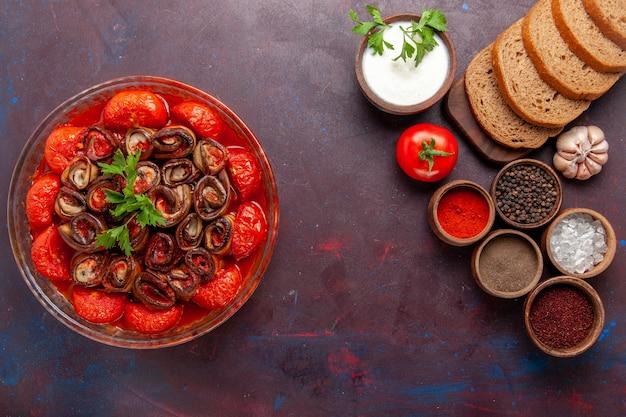Vista dall'alto farina di verdure cotte pomodori e melanzane con condimenti e pane sulla scrivania scura