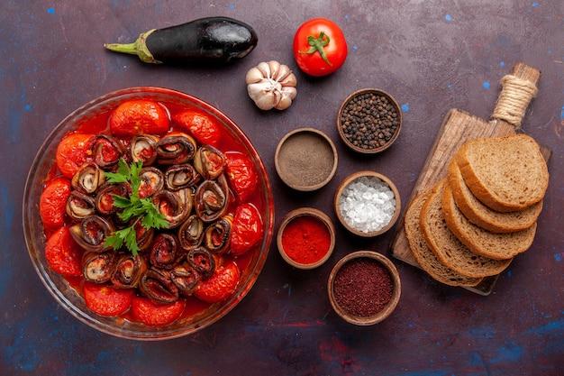 Vista dall'alto farina di verdure cotte pomodori e melanzane con pane condimenti sulla superficie scura