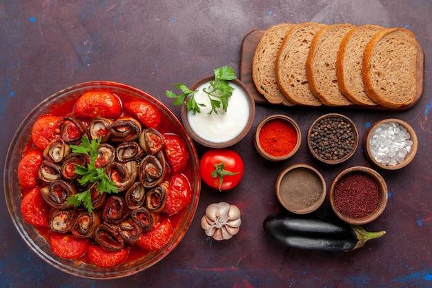 Vista dall'alto farina di verdure cotte pomodori e melanzane con condimenti e pagnotte di pane sulla scrivania scura