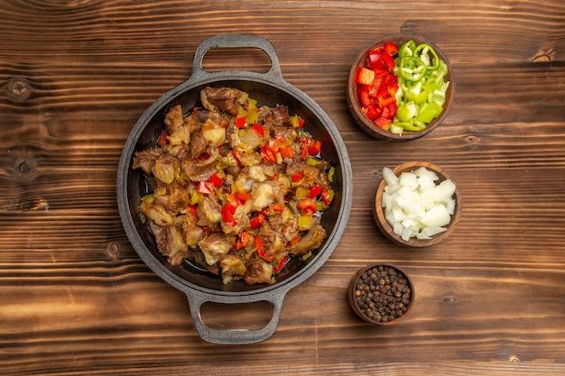 Вид сверху приготовленная овощная еда с мясом и свежим нарезанным болгарским перцем на деревянном коричневом столе
