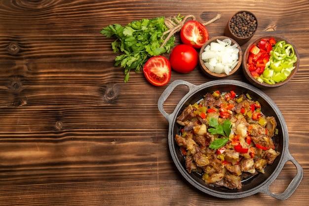 木製の茶色の机の上に肉と緑と野菜の食事を調理した上面図