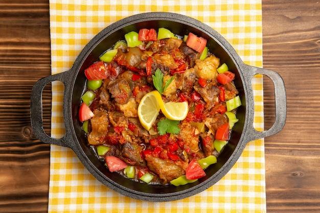 Вид сверху приготовленной овощной еды с мясом и нарезанным болгарским перцем внутри сковороды на коричневом столе