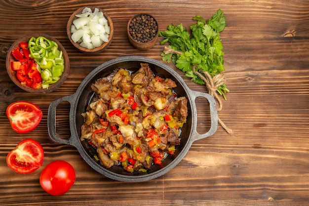Top view cooked vegetable meal with meat and fresh sliced bell-pepper on the wooden brown desk