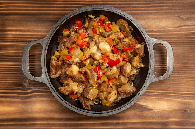 Top view cooked vegetable meal with meat and sliced bell peppers on the brown desk