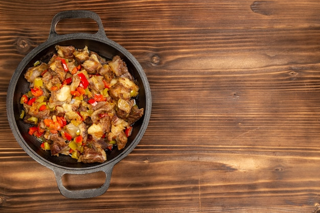 Top view cooked vegetable meal with meat and sliced bell peppers on the brown rustic desk