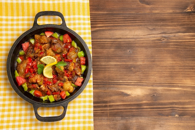 Top view cooked vegetable meal with meat and sliced bell-peppers inside pan on the brown wooden desk
