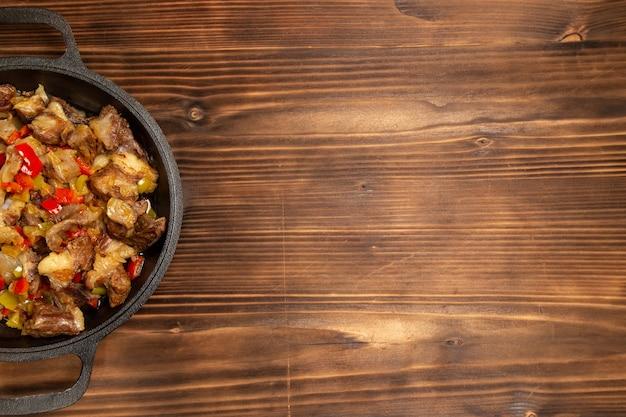 Vista dall'alto pasto di verdure cotte con carne e peperoni affettati sulla scrivania in legno