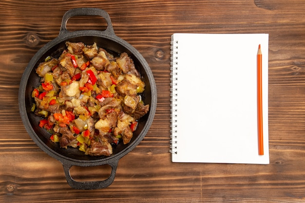 Top view cooked vegetable meal with meat and with notepad on the wooden desk