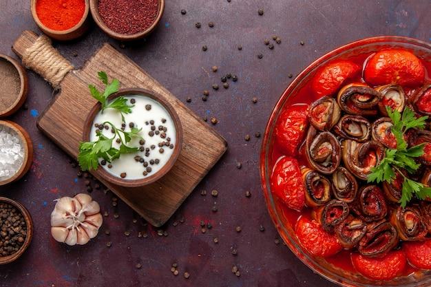 어두운 표면에 조미료와 사워 크림이 들어간 상위 뷰 조리 야채 식사