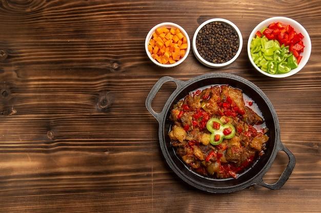 Vista dall'alto pasto di verdure cotte con condimenti e pepe a fette sulla scrivania marrone
