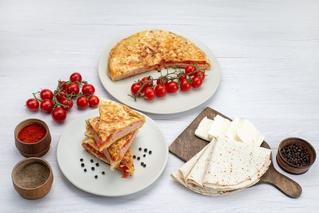 Top view cooked vegetable pastry round inside white plate along with white cheese and tomatoes white background meal food pastry lunch greens