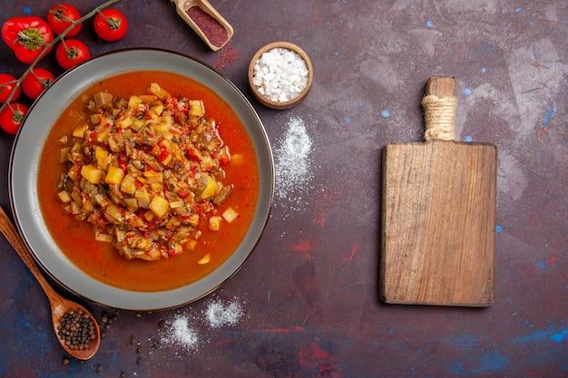 Vista dall'alto di verdure cotte affettate con salsa sulla scrivania scura salsa pasto cena cibo zuppa di verdure