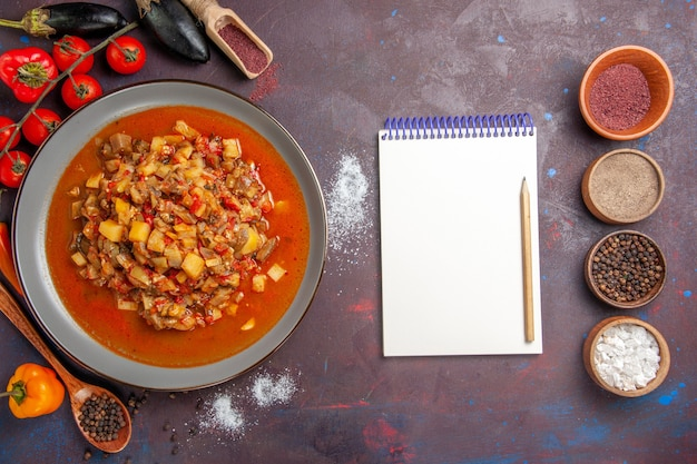 Vista dall'alto di verdure cotte affettate con salsa e condimenti sul pavimento scuro pasto cena zuppa di verdure salsa di verdure