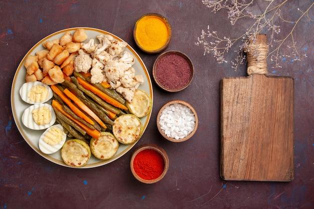 暗い机の上に卵の食事と調味料と一緒に調理された野菜の上面図